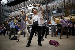 """Elderly and middle-age people exercise with wooden dumbbells during a health promotion event to mark Japan's """"Respect for the Aged Day"""" at a temple in Tokyo"""