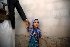 A girl holds her father's hand after she received polio vaccine drops during a house-to-house vaccination campaign in Yemen's capital Sanaa