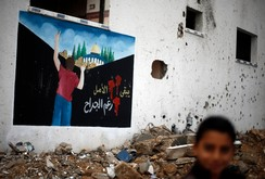 Palestinian boy walks past a mural depicting the Dome of the Rock painted on a house which witnesses said was damaged by Israeli shelling during the most recent conflict between Israel and Hamas, in the east of Gaza City