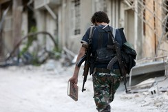 A Free Syrian Army fighter carries a copy of the Koran as he walks along a street in Jobar, a suburb of Damascus, Syria