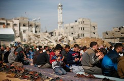 Palestinians attend Friday prayers near the ruins of houses that witnesses said were destroyed or damaged by Israeli shelling during a 50-day war last summer, in the Shejaia neighbourhood east of Gaza City