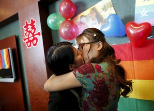 Li Tingting (L) and Teresa kiss at their wedding reception in Beijing, China