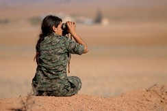 A female fighter of the Kurdish People's Protection Units (YPG) uses a pair of binoculars as she looks towards areas controlled by Islamic State fighters in the southern countryside of Ras al-Ain