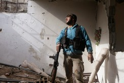 A Free Syrian Army fighter inside a damaged room in Jobar, Syria