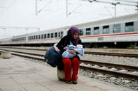 Migrant feeds a child before they board a train, Croatia