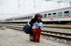 A migrant feeds a child before they board a train at the railway station in Tovarnik, Croatia