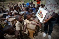 A man shows a picture to students during a UNICEF Ebola awareness drive in Gueupleu, Man