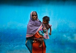 Bedan Bai, 70, the mother of a victim who died after undergoing a sterilization surgery at a government mass sterilization camp, holds her granddaughter Kirti outside her house, India, November 15, 2014
