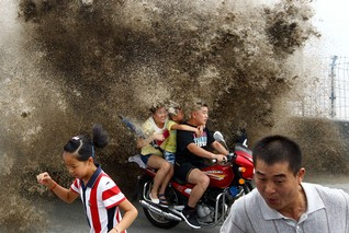 Visitors run away as waves caused by a tidal bore surge past a barrier on the banks of Qiantang River, in Hangzhou, Zhejiang province August 13, 2014