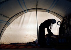 A Kurdish refugee woman from Kobani tends to her child inside her tent at a refugee camp in the border town of Suruc, Sanliurfa province November 7, 2014