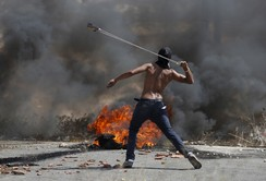 A Palestinian protester uses a sling to hurl stones towards Israeli troops during clashes near the Jewish settlement of Bet El, near the occupied West Bank city of Ramallah