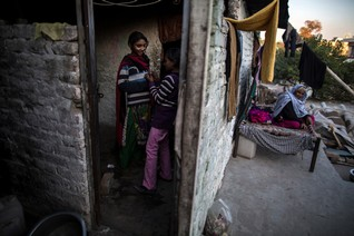 Girls talk to each other in their one-room shack while their grandmother sits outside, in a Christian slum in Islamabad December 4, 2014