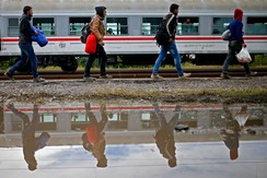 Migrants walk to board a train at the railway station in Tovarnik, Croatia