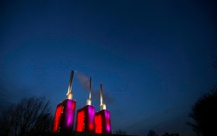 "The so-called ""three warm brothers"" of the combined heat and power plant Linden of Hanover's public utility company Enercity is illuminated with red and purple lights during the twilight hour in the central German town of Hanover November 26, 2014"