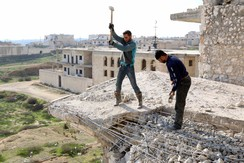 Men work on a damaged building at al-Hamidiya area, Syria