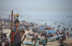 Palestinian boys standing behind a fence watch people as they enjoy the warm weather on Gaza City beach along the Mediterranean Sea