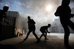 Palestinian protesters prepare to throw stones at Israeli army soldiers during clashes following an anti-Israel demonstration in solidarity with al-Aqsa mosque, in Hebron