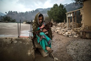 A girl holds a goat outside her house on Margalla Hills in Islamabad