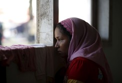 A Rohingya migrant who arrived in Indonesia this week by boat looks out the window of a temporary shelter in Aceh Timur regency, near Langsa in Indonesia's Aceh Province May 24, 2015