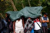Migrants from Cameroon protect themselves from rain, Hungary