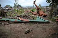 A boy does a flip in the coastal part of Tacloban, that was destroyed by Typhoon Haiyan