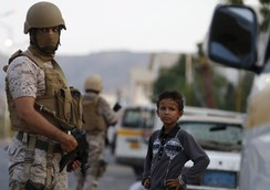 Boy stands next to soldiers from the Saudi-led coalition securing a street in Yemen's southern port city of Aden