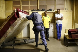 A fender is seen during a police search as local residents look at a police officer during a raid on a hostel in Johannesburg's Alexandra township