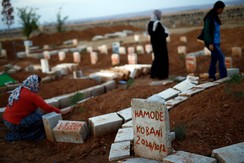 Women mourn near graves of Kurdish fighters who died in Kobani, near the southeastern town of Suruc in Sanliurfa province, on the Turkish-Syrian border October 15, 2014