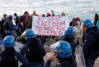 Migrants and activists hold a banner as they face off with Italian police on the seawall at the Saint Ludovic border crossing on the Mediterranean Sea between Ventimiglia, Italy and Menton, France