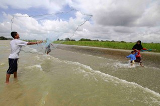 A man casts a fishing net as residents make their way on a flooded road in the Pattani province, Thailand