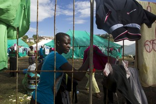 A foreign woman from Zimbabwe fetches dry clothes from the fence at a camp set up to house those affected by anti-immigrant violence in Chatsworth