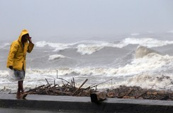 A man walks along the coast at a port, after heavy rain and strong winds brought by typhoon Hagupit battered Atimonan town