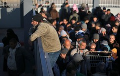 A Palestinian man, hoping to cross into Egypt, climbs a gate as he waits at the Rafah crossing between Egypt and the southern Gaza Strip January 20, 2015.