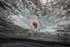 A woman is seen through a crack in a car window, that was hit by shrapnel, near a residential block of flats which was damaged by a recent shelling in Donetsk