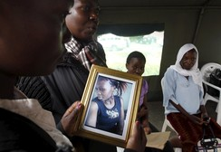 Relative carries a picture of a student killed in Thursday's attack by gunmen, at the Chiromo Mortuary in Kenya's capital Nairobi