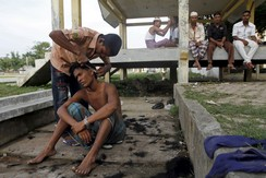 Migrants, believed to be Rohingya, cut each others' hair inside a shelter after being rescued from boats at Lhoksukon, in Indonesia's Aceh Province May 12, 2015