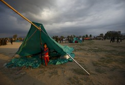 A child stands inside a makeshift shelter in an open ground to keep safe after an earthquake in Kathmandu