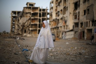 A Palestinian girl stands near residential buildings that witnesses said were heavily damaged by Israeli shelling during a 50-day war last summer, in Beit Lahiya town in the northern Gaza Strip May 25, 2015