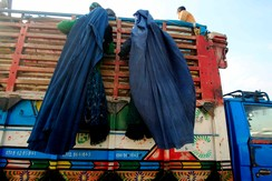 Afghan refugee women, clad in a burqa, climb on a truck to be repatriated to Afghanistan at the UNHCR office on the outskirts of Peshawar