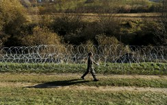 A Slovenian soldier walk next to a wire fence in the village of Veliki Obrez, Slovenia