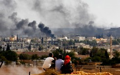 Kurdish refugees from Kobani watch as thick smoke covers the Syrian town of Kobani during fighting between Islamic State and Kurdish Peshmerga forces