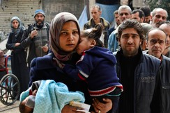 Residents queue up to receive humanitarian aid at the Palestinian refugee camp of Yarmouk, in Damascus March 11, 2015.