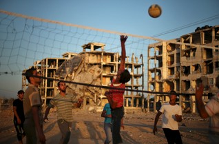 Palestinians play volleyball near residential buildings, that witnesses said were heavily damaged by Israeli shelling during a 50-day war last summer, in Beit Lahiya town in the northern Gaza Strip May 20, 2015