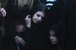 Sahar, the girlfriend of Israeli soldier Dor Nini mourns next to his fresh grave during his funeral in a cemetery at Shtulim village near Ashdod