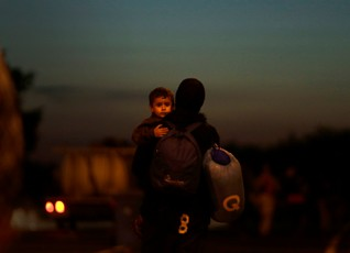 A migrant carries a child after crossing the Austrian-Hungarian border into Nickelsdorf, Austria