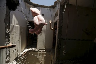 A worker throws a stuffed toy to another as they move furniture from a house damaged after an air strike by a Saudi-led coalition struck a nearby missile base, in Yemen's capital Sanaa