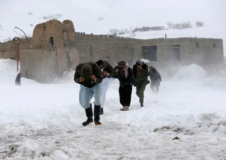 Afghan survivors of an avalanche run to get relief goods distributed by an Afghan army helicopter in the Paryan district of Panjshir province