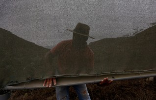 Landowner and farmer Teofilo Huamani stands next to a net that traps moisture from fog on the hillside of Villa Maria Del Triunfo in Lima, November 20, 2014