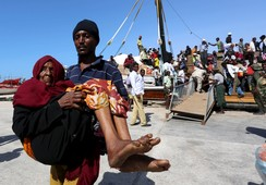 A man carries an elderly woman from a ship that has arrived, carrying people fleeing violence in Yemen, at the port of Bosasso in Somalia's Puntland region
