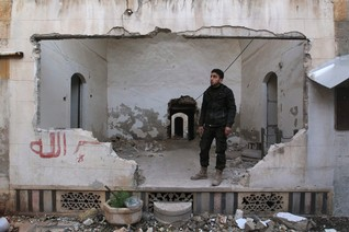 A rebel fighter stands inside a damaged room near the frontline against forces loyal to Assad in Aleppo